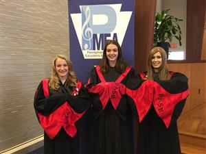 three students in choral gowns